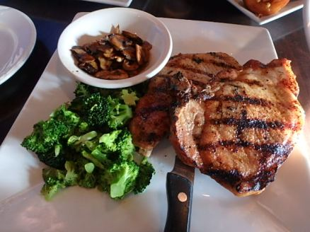 Pork chop dinner with sauteed mushrooms and broccoli